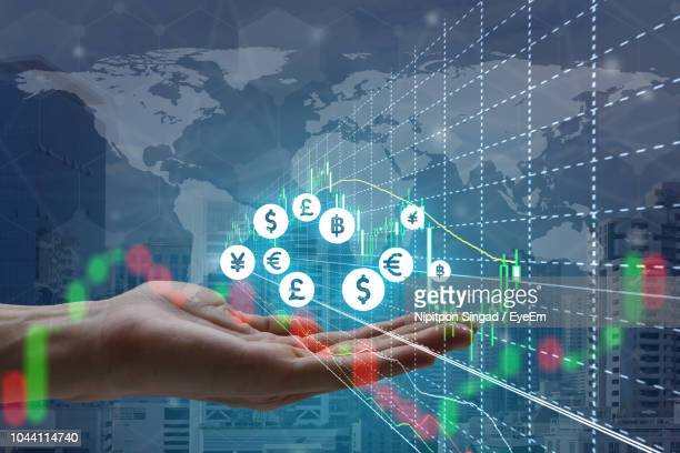 digital composite image of hand gesturing by icons with world map in background - currency symbol stock pictures, royalty-free photos & images