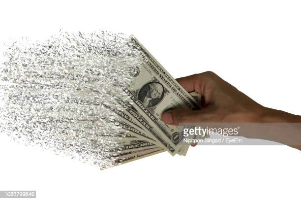 digital composite image of hand holding currency over white background - fading stock pictures, royalty-free photos & images