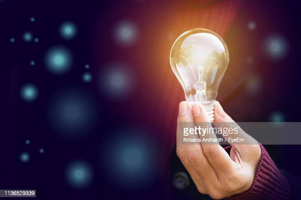 digital composite image of hand holding illuminated light bulb - power supply stock pictures, royalty-free photos & images