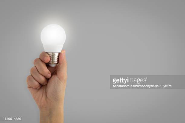 digital composite image of hand holding illuminated light bulb against white background - light bulb stock pictures, royalty-free photos & images