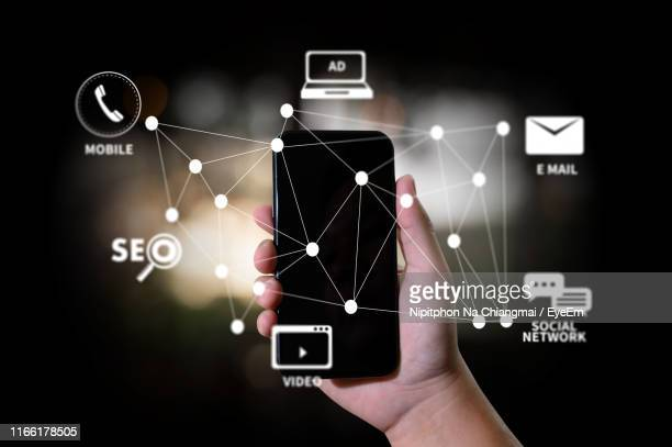 digital composite image of hand holding mobile phone with various icons in darkroom - search engine stock pictures, royalty-free photos & images