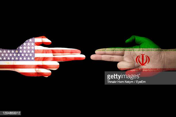 digital composite image of hand with flag against black background - iran stock pictures, royalty-free photos & images