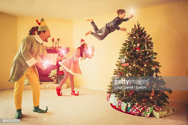 Digital Composite Image Of Happy Family Decorating Christmas Tree At Home