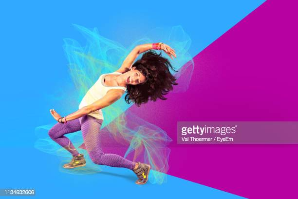 digital composite image of happy woman dancing against colored background - bearbeitungstechnik stock-fotos und bilder