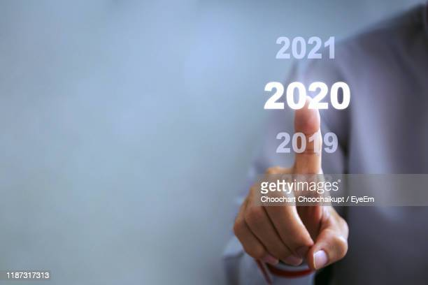 digital composite image of human hand touching numbers on screen - 2020 stock pictures, royalty-free photos & images