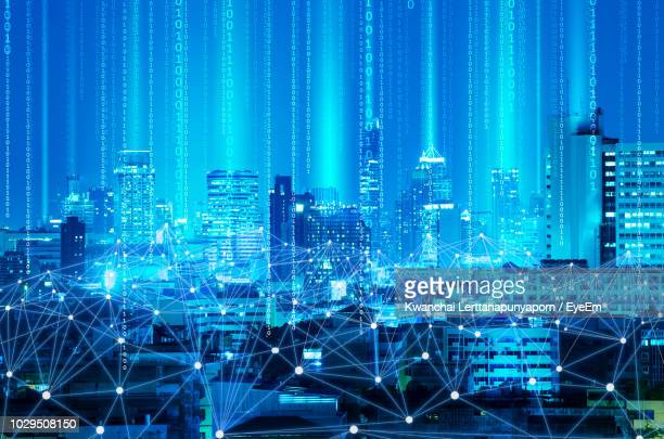 digital composite image of illuminated cityscape with binary numbers at night - binary code stock pictures, royalty-free photos & images