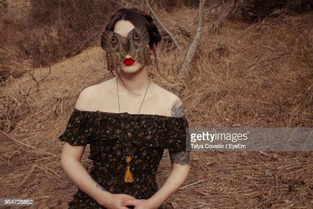 Digital Composite Image Of Large Butterfly On Young Woman Standing Against Tree