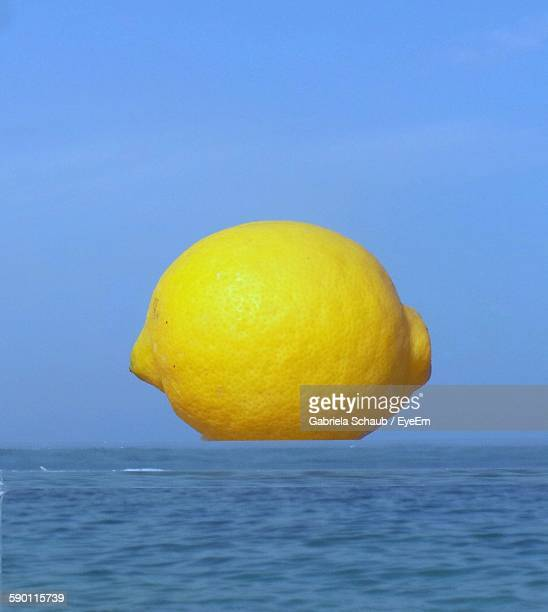 Digital Composite Image Of Lemon And Sea Against Clear Sky