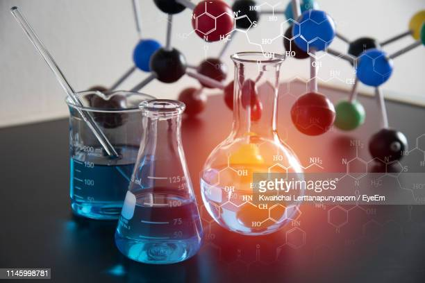 digital composite image of liquids and molecular structure on table - chemistry stock pictures, royalty-free photos & images