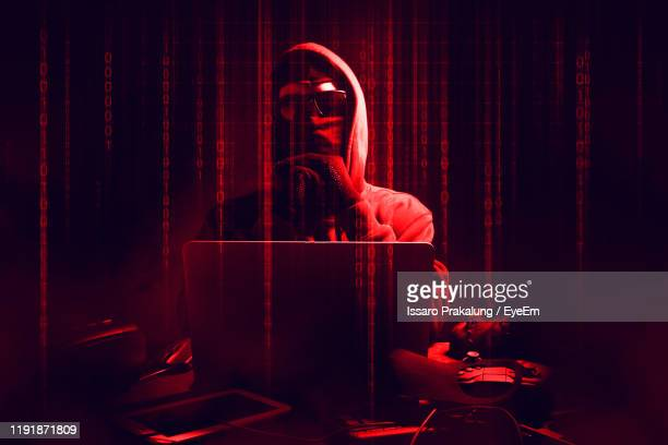 digital composite image of male hacker using laptop with binary codes in darkroom - hacker stock pictures, royalty-free photos & images
