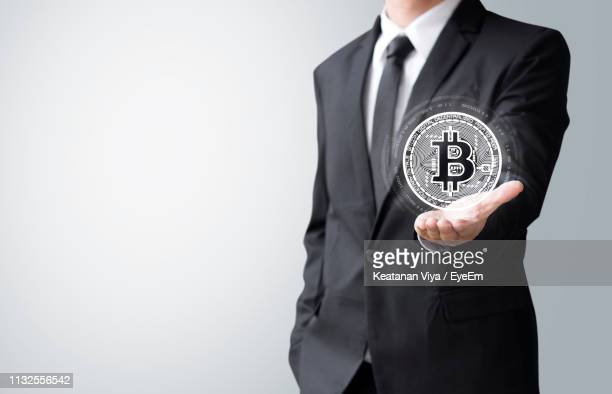 digital composite image of man holding bitcoin against white background - bitcoin stock pictures, royalty-free photos & images