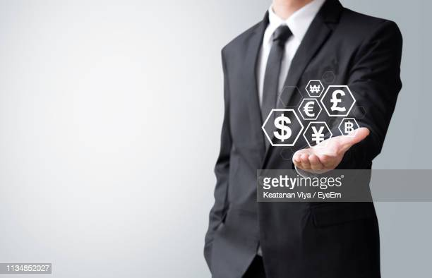 digital composite image of man holding currency symbols against white background - crypto monnaie photos et images de collection