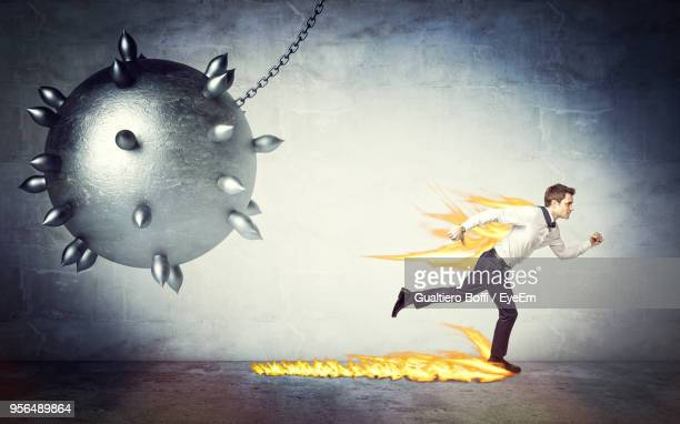 Digital Composite Image Of Man In Fire Running From Spiked Sphere Against Wall