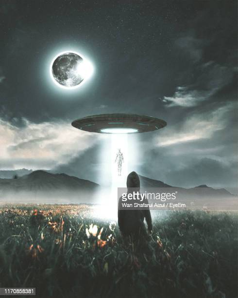 digital composite image of man looking at ufo flying over field against sky - ovni photos et images de collection