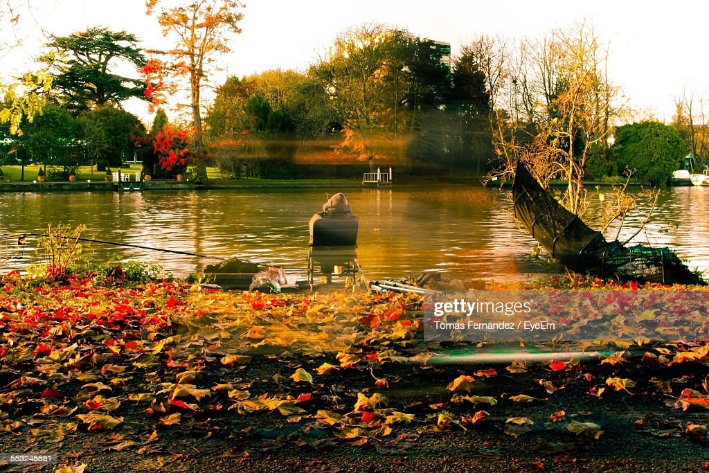 Digital Composite Image Of Man Sitting By River Against Sky : Stock Photo