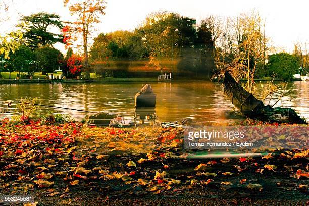 digital composite image of man sitting by river against sky - kingston upon thames stock pictures, royalty-free photos & images