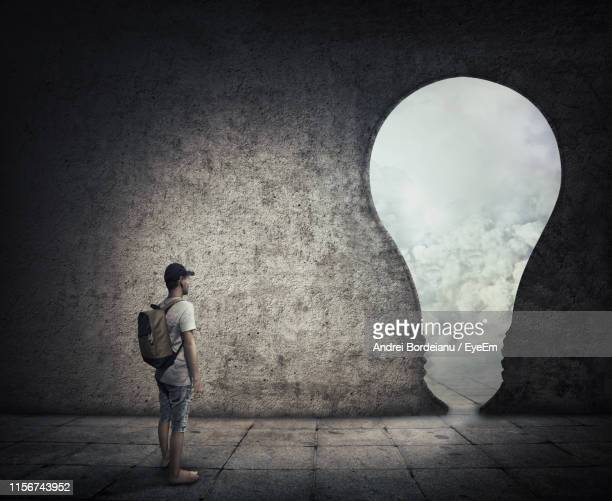 digital composite image of man standing by light bulb shape in wall - デジタル合成 ストックフォトと画像
