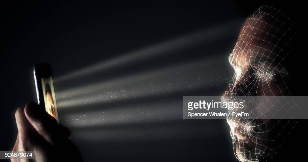 digital composite image of man using mobile phone in darkroom - biometrics stock photos and pictures