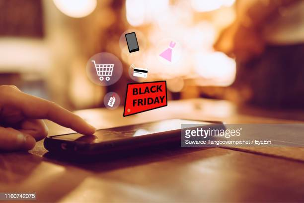 digital composite image of man using smart phone on table - black friday stock photos and pictures