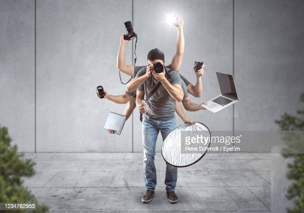 digital composite image of man with multiple hands holding various objects - multi tasking stock pictures, royalty-free photos & images