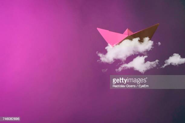 Digital Composite Image Of Paper Boat On Clouds Against Pink Background