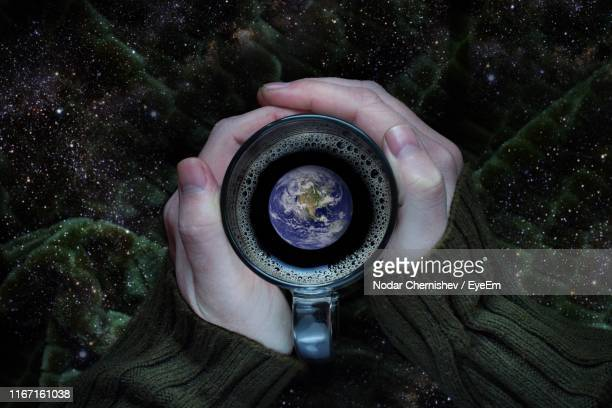 digital composite image of person holding coffee cup with planet earth in drink - coffee drink stock pictures, royalty-free photos & images