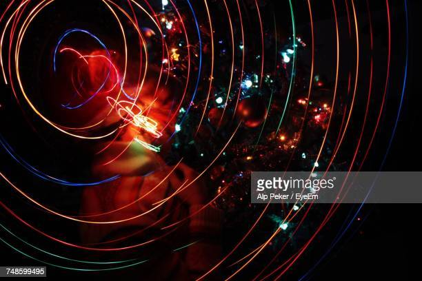 Digital Composite Image Of Person Surrounded With Spiral Light Trails At Night