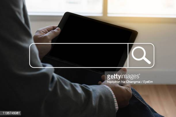 digital composite image of search symbol against businessman holding digital tablet - searching stock pictures, royalty-free photos & images