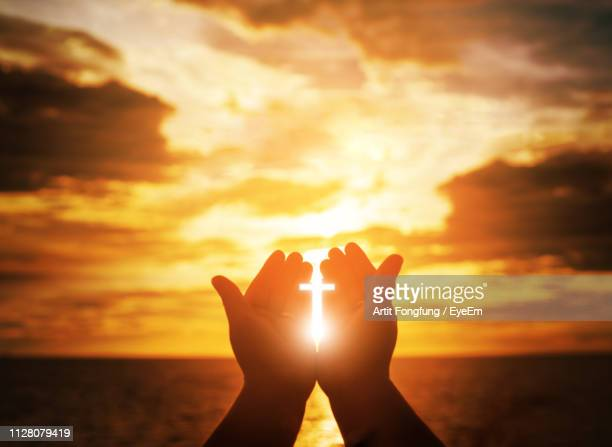 digital composite image of silhouette hand holding sunlight cross against sky - resurrection religion stock pictures, royalty-free photos & images