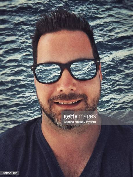 Digital Composite Image Of Smiling Man Against Sea With Wave Reflection On Sunglasses