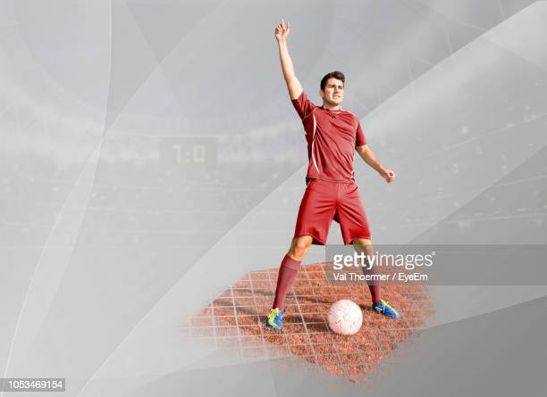 digital composite image of soccer player with ball standing in stadium - traje de fútbol fotografías e imágenes de stock