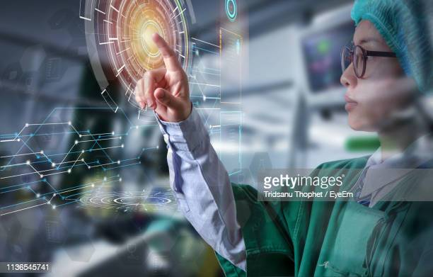 digital composite image of surgeon touching interface - touch screen stock pictures, royalty-free photos & images