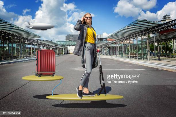 digital composite image of teenage girl with luggage levitating over street - val thoermer stock-fotos und bilder