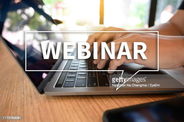 digital composite image of webinar text against cropped hand using laptop at desk - web conference stock pictures, royalty-free photos & images