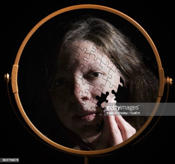 Digital Composite Image Of Woman Holding Face Puzzle Piece