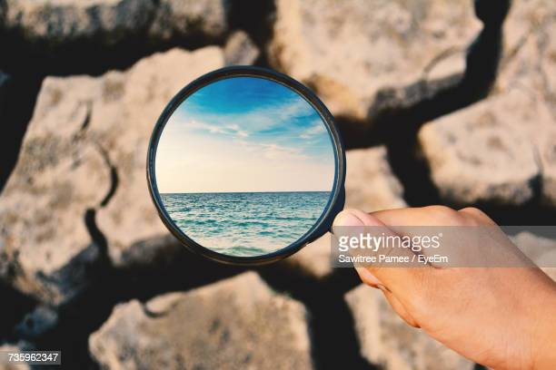 Digital Composite Image Of Woman Holding Magnifying Glass With Reflection Of Sea Over Barren Land