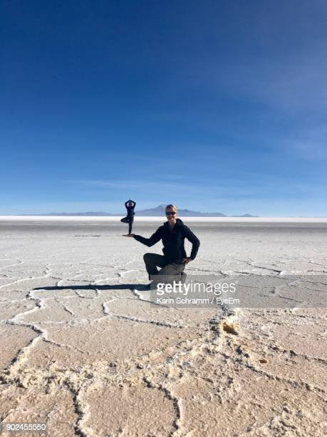 digital composite image of woman holding man while kneeling on salt flat against blue sky - salt flat stock pictures, royalty-free photos & images