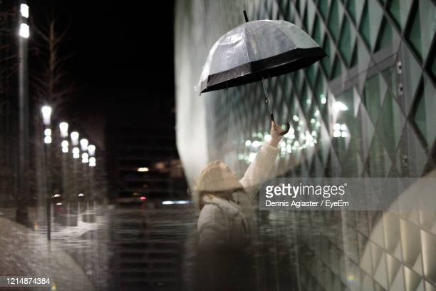 digital composite image of woman holding umbrella standing by building in city - storm dennis stock pictures, royalty-free photos & images
