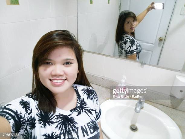Digital Composite Image Of Woman Taking Selfie With Reflection On Mirror In Bathroom
