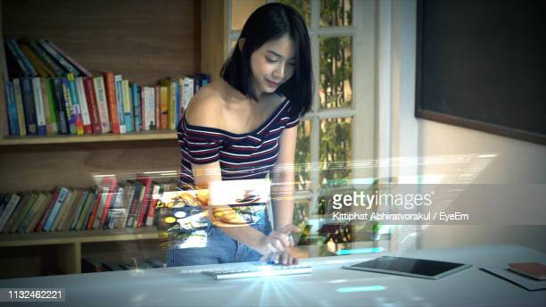 Digital Composite Image Of Woman Using Computer At Table