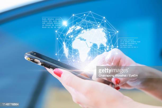 digital composite image of woman using mobile phone by globe - digital composite stock pictures, royalty-free photos & images