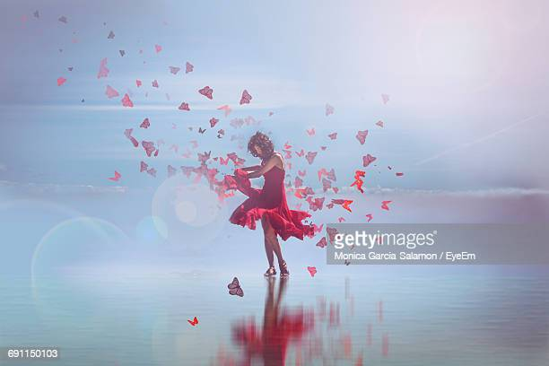digital composite image of woman wearing red dress dancing with butterflies on shore - digital composite stock pictures, royalty-free photos & images