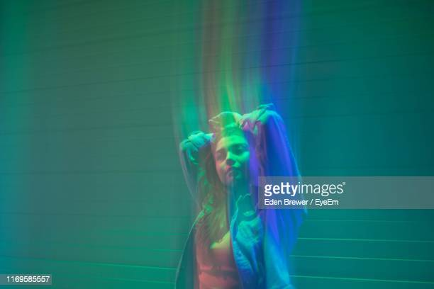 digital composite image of woman with hand in hair and illuminated against wall - people stock pictures, royalty-free photos & images