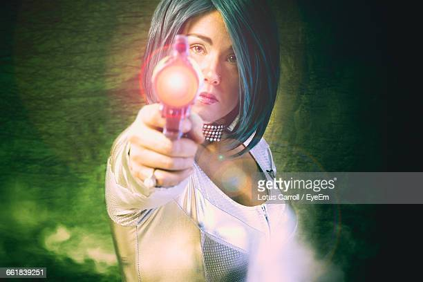 Digital Composite Image Of Woman With Laser Gun