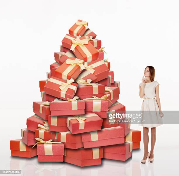 digital composite image of young woman standing by piled gifts against white background - grote groep dingen stockfoto's en -beelden