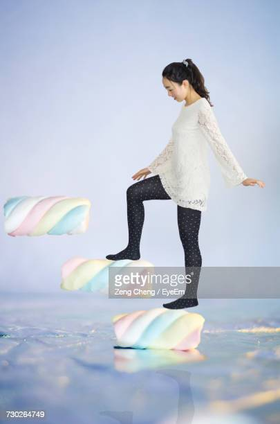 Digital Composite Image Of Young Woman Stepping On Marshmallows Against White Background