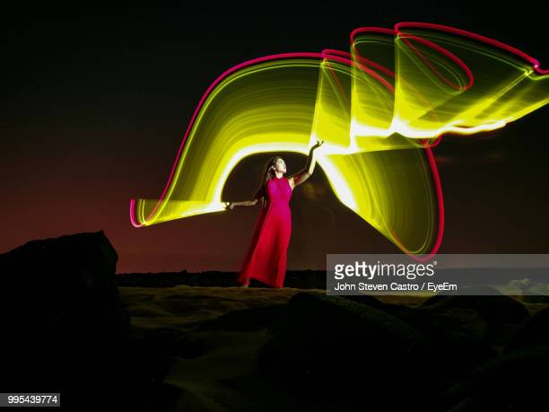 digital composite image of young woman with illuminated light paintings standing against sky at night - lichtmalerei stock-fotos und bilder