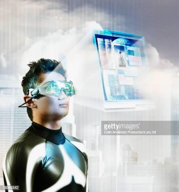 Digital composite of Asian man wearing hologram display glasses