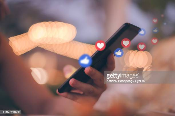 digital composite of cropped woman hand using smart phone by social media icons against illuminated lights - social network foto e immagini stock