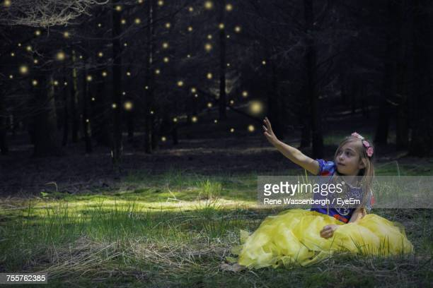 digital composite of girl in snow white costume sitting on grassy field with hand raised against fireflies - snow white stock photos and pictures